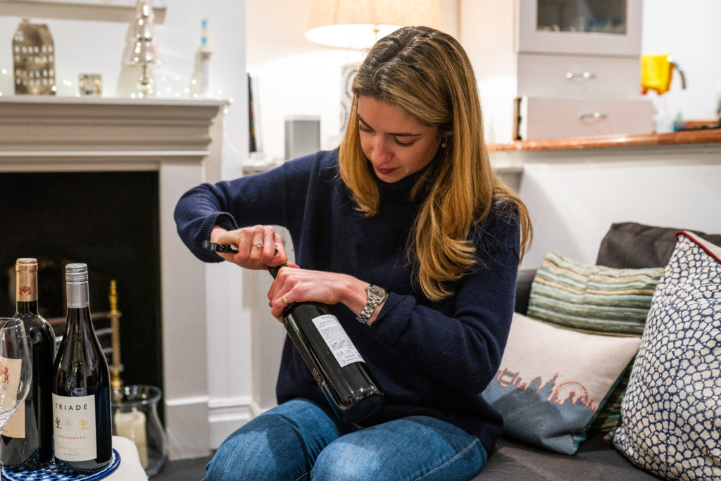 Pippa opening a bottle of wine
